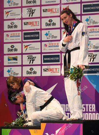 Bianca Walkden of Great Britain receives the Gold medal in the Womens 73kg Final fight after beating Shuyin Zheng of China  after she was disqualified and then collapses on the podium.