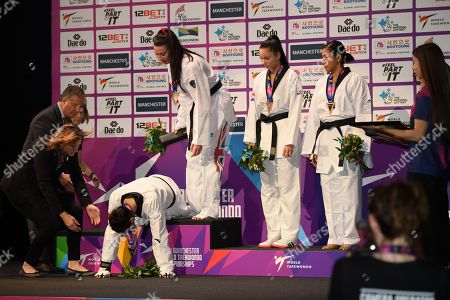Shuyin Zheng of China collapses on the podium after being disqualified during the 73kg final with Bianca Walkden of Great Britain.