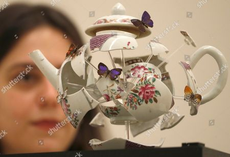 Stock Image of A Christies employee looks at a an art work by Bouke De Vries entitled 'Deconstructed Teapot with Butterflies' 2017, at Christie's auction house in London, . The teapoat is expected to sell for some 4-6,000 pounds sterling (US$ 5,100-7,600) at auction on Mat 22
