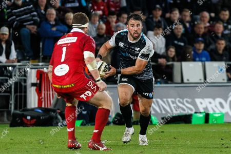 Stock Picture of Scott Baldwin of the Ospreys takes on Phil Price of the Scarlets
