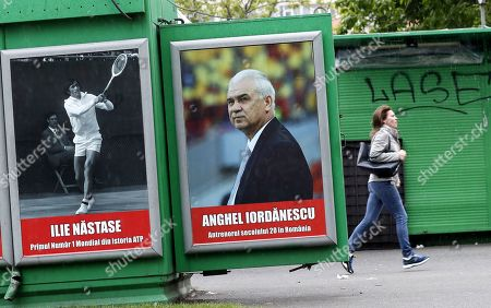 People pass a newspaper stand, decorated with portraits of EU Parliament candidates, without EU or party logo, prior to the European Parliament elections, in central Bucharest, Romania, 17 May 2019. The poster on the left depicts Ilie Nastase, 73, former tennis star and first ATP ranked No. 1 tennis player, and the right one shows Anghel Iordanescu, 69, former footballer and manager of national soccer team of Romania. Nastase and Iordanescu occupy the first positions on the EU Parliament candidates list for the National Union for the Progress of Romania (UNPR). Romanians will vote their representatives for the European Union Parliament on 26 May 2019. The banner on the center reads 'Ilie Nastase, first world no 1 from ATP history', and the right one writes 'Anghel Iordanscu, the soccer manager of the 20th century in Romania'.