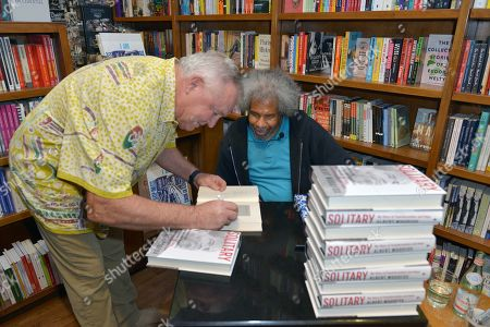 "Stock Picture of Author Les Standiford signing a copy of his book to Former ""Angola 3"" inmate Albert Woodfox after Albert book signing of ""Solitary"" at Books & Books"