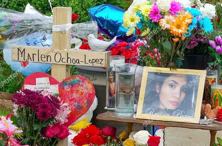 A memorial of flowers, balloons, a cross and photo of victim Marlen Ochoa-Lopez, are displayed on the lawn, in Chicago, outside the home where Ochoa-Lopez was murdered last month. Assistant State's Attorney James Murphy says a pregnant Ochoa-Lopez, who was killed and whose baby was cut from her womb, was strangled while being shown a photo album of the late son and brother of her attackers