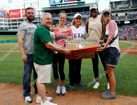 Stock Picture of Baylor women's basketball head coach Kim Mulkey third from right, is presented with a cookie cake after throwing out the ceremonial first pitch before a baseball game between the St. Louis Cardinals and the Texas Rangers in Arlington, Texas, . Presenting the cake to Mulkey are, from left to right, son-in-law Clay Fuller, member of her staff Johnny Derrick, grandson Kannon Reid Fuller, daughter Makenzie Fuller, an unidentified person, and member of her staff Jennifer Roberts