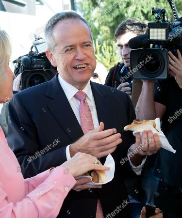 Australian opposition leader Bill Shorten and his wife Chloe eat a sausage sandwich on a federal election day in Melbourne, Australia, . Polling stations opened across Australia on Saturday in elections that are likely to deliver the nation's sixth prime minister in as many years