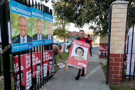 A supporter of Labor candidate for Cowan Anne Aly is seen carrying her election poster outside a polling station at Landsdale Primary School on Election Day in Perth, Australia, 18 May 2019. Approximately 16.5 million Australians will vote in what is tipped to be a tight election contest between Australian Prime Minister Scott Morrison and Australian Opposition Labor leader Bill Shorten.