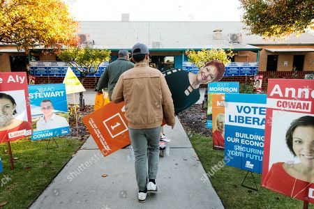 A Pauline Hanson supporter carries an election poster of her into a polling station at Landsdale Primary School on Election Day in Perth, Australia, 18 May 2019. Approximately 16.5 million Australians will vote in what is tipped to be a tight election contest between Australian Prime Minister Scott Morrison and Australian Opposition Labor leader Bill Shorten.