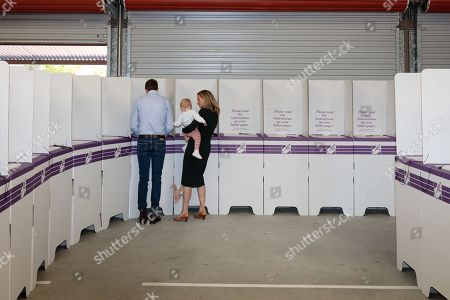 Liberal candidate Christian Porter (L) votes as his wife, Jen and daughter Florence look on at Ellen Stirling Primary School on Election Day in Perth, Australia, 18 May 2019. Approximately 16.5 million Australians will vote in what is tipped to be a tight election contest between Australian Prime Minister Scott Morrison and Australian Opposition Labor leader Bill Shorten.