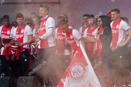Ajax director and former goalkeeper Edwin van der Sar, fourth from left, catches a beer can thrown by fans at Amsterdam mayor Femke Halsema, second right, as Ajax players celebrate clinching the Dutch Premier League soccer title in Amsterdam, Netherlands, . A Dutch newspaper reported that Dutch police had asked Van der Sar and captain Matthijs de Ligt, right, to watch over Halsema when she addressed the crowd