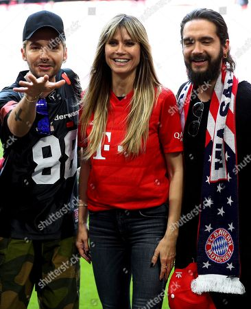 Former German model Heidi Klumm, center, her partner and member of the band 'Tokio Hotel', Tom Kaulitz, right, and Tom's brother Bill Kaulitz, left, pose for the media prior to the German Bundesliga soccer match between FC Bayern Munich and Eintracht Frankfurt in Munich, Germany