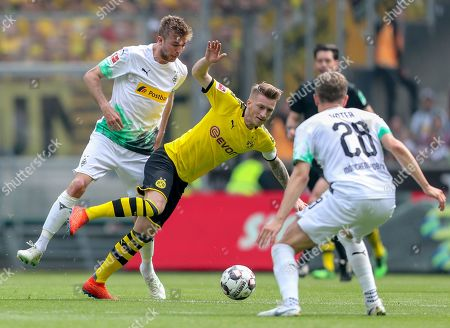 Moenchengladbach's Christoph Kramer (R) in action with Dortmund's Marco Reus (2-R) during the German Bundesliga soccer match between Borussia Moenchengladbach and Borussia Dortmund at Borussia-Park in Moenchengladbach, Germany, 18 May 2019.