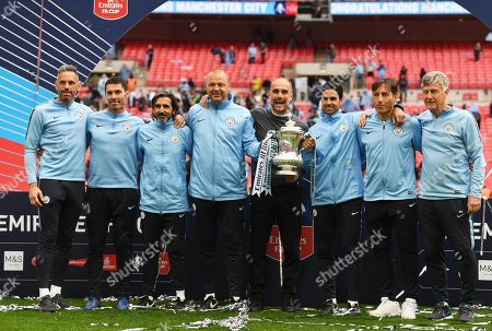 REPEAT OF epa07582282 with full IDs Manchester City manager Pep Guardiola (C grey jumper) and his coaching staff pose with the trophy after the English FA Cup final between Manchester City and Watford at Wembley Stadium in London, Britain, 18 May 2019. (reissued 20 May 2019). Others are from left: Under-18 goalkeeping coach and former player Richard Wright, Xabi Mancisidor (goalkeeper coach), Lorenzo Buenaventura (fitness coach), Rodolfo Borrell (assistant coach), Mikel Arteta (assistant coach), Carles Planchart (performance analyst) and Brian Kidd (assistant coach).