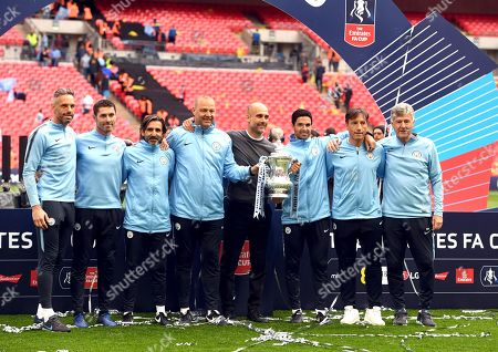 Stock Picture of Manchester City manager Pep Guardiola (C grey jumper) and his coaching staff pose with the trophy after the English FA Cup final between Manchester City and Watford at Wembley Stadium in London, Britain, 18 May 2019. (reissued 20 May 2019). Others are from left: Under-18 goalkeeping coach and former player Richard Wright, Xabi Mancisidor (goalkeeper coach), Lorenzo Buenaventura (fitness coach), Rodolfo Borrell (assistant coach), Mikel Arteta (assistant coach), Carles Planchart (performance analyst) and Brian Kidd (assistant coach).
