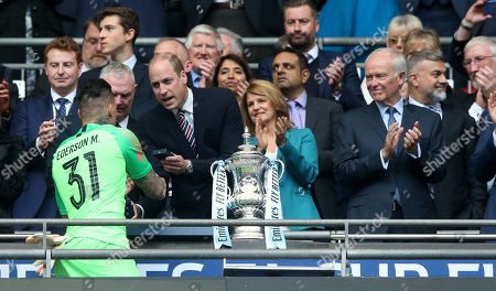 The President of Emirates Airline, Sir Tim Clark (R), Greg Clarke, FA Chairman, HRH Prince William, present the Emirates FA Cup winners' medal to Ederson of Manchester City