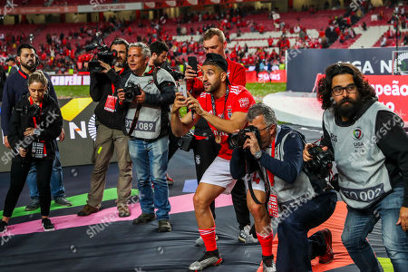 Benfica player Adel Taarabt (C) takes a photo next to photographers during the celebration after their 37th title of the Portuguese First League after winning Santa Clara (4-1) at Luz Stadium in Lisbon, Portugal, 18 May 2019.