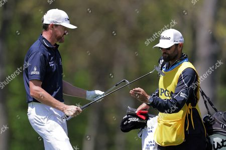 Jimmy Walker takes a putter from his caddie after chipping onto the ninth green during the third round of the PGA Championship golf tournament, at Bethpage Black in Farmingdale, N.Y