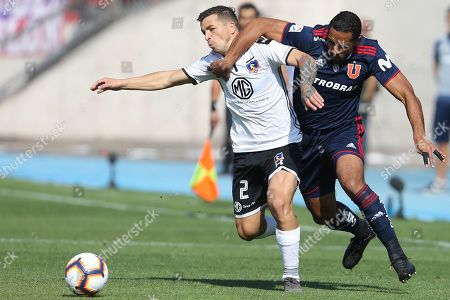 Jean Beausejour (R) of Universidad de Chile vies for the ball with Gabriel Costa (L) of Colo-Colo during a match for the First Division of Chilean soccer, at the National Stadium, in Santiago, Chile, 18 May 2019.