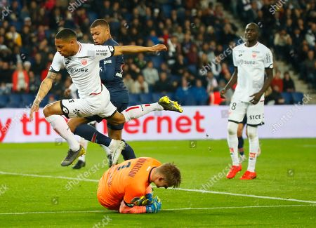 Dijon's Mickael Alphonse, left, challenges for the ball with PSG's Kylian Mbappe as Dijon goalkeeper Runar Alex Runarsson makes a save during their League One soccer match between Paris Saint Germain and Dijon at the Parc des Princes stadium in Paris, France