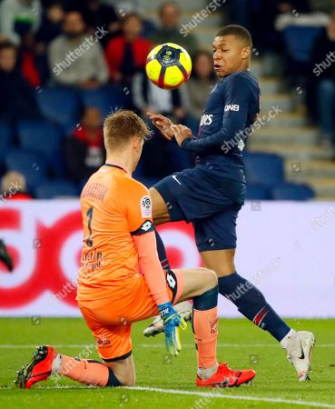 Dijon goalkeeper Runar Alex Runarsson, left, challenges for the ball with PSG's Kylian Mbappe during their League One soccer match between Paris Saint Germain and Dijon at the Parc des Princes stadium in Paris, France