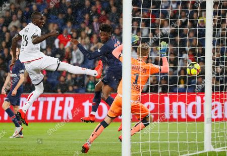 Stock Photo of PSG'S Lois Mbe Soh, centre, heads the ball ahead of Dijon goalkeeper Runar Alex Runarsson, right, and Dijon's Cedric Yambere during their League One soccer match between Paris Saint Germain and Dijon at the Parc des Princes stadium in Paris, France