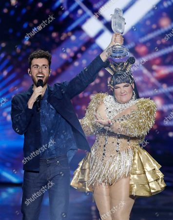 """Duncan Laurence of the Netherlands celebrates with the trophy after winning the 2019 Eurovision Song Contest grand final with the song """"Arcade"""" in Tel Aviv, Israel, . In rear is Israeli Netta Barzilai the winner in 2018"""