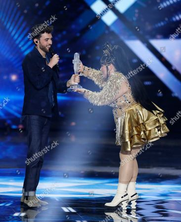 """Duncan Laurence of the Netherlands receives the trophy from Israeli Netta Barzilai, the winner in 2018, after winning the 2019 Eurovision Song Contest grand final with the song """"Arcade"""" in Tel Aviv, Israel"""