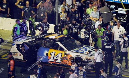 A NASCAR official tries to get between drivers Ryan Newman, in green suit near the car's hood, and Clint Bowyer after the NASCAR All-Star Race at Charlotte Motor Speedway in Concord, N.C