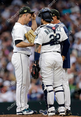 Seattle Mariners starting pitcher Wade LaBlanc, left, talks on the mound with catcher Omar Narvaez and pitching coach Paul Davis during the second inning against the Minnesota Twins in a baseball game, in Seattle