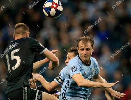 Andy Rose, Seth Sinovic. Vancouver Whitecaps midfielder Andy Rose (15) heads the ball over Sporting Kansas City defender Seth Sinovic, right, during the first half of an MLS soccer match in Kansas City, Kan