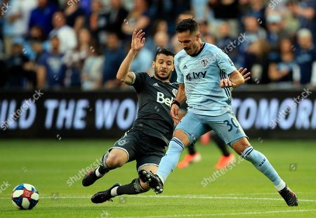 Benny Feilhaber, Felipe Martins. Sporting Kansas City midfielder Benny Feilhaber (30) is tackled by Vancouver Whitecaps midfielder Felipe Martins, left, during the first half of an MLS soccer match in Kansas City, Kan., . Martins received a yellow card on the play