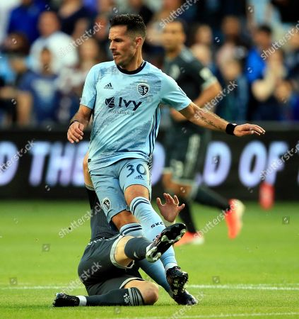 Benny Feilhaber, Felipe Martins. Sporting Kansas City midfielder Benny Feilhaber (30) is tackled by Vancouver Whitecaps midfielder Felipe Martins, back, during the first half of an MLS soccer match in Kansas City, Kan., . Martins received a yellow card on the play