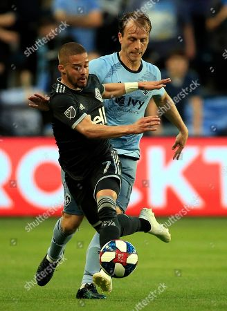Lucas Venuto, Seth Sinovic. Vancouver Whitecaps midfielder Lucas Venuto (7) plays the ball in front of Sporting Kansas City defender Seth Sinovic, right, during the first half of an MLS soccer match in Kansas City, Kan