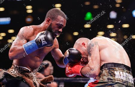 Gary Russell Jr., left, punches Spain's Kiko Martinez during the fourth round of the WBC featherweight championship boxing match, in New York. Russell stopped Martinez in the fifth round