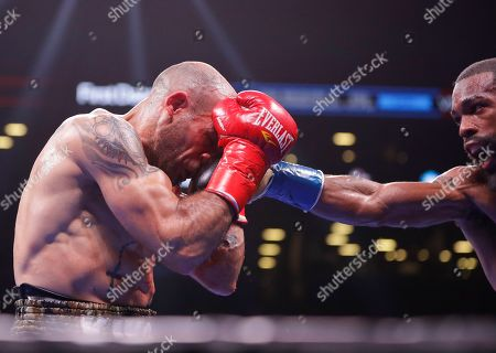 Gary Russell Jr., right, punches Spain's Kiko Martinez during the fifth round of the WBC featherweight championship boxing match, in New York. Russell stopped Martinez in the fifth round