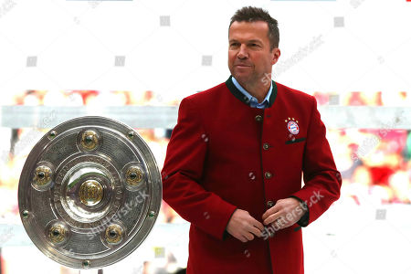 Former Bayern player Lothar Matthaus hands over the trophy after winning Bayern's 7th straight Bundesliga title after the German Soccer Bundesliga match between FC Bayern Munich and Eintracht Frankfurt in Munich, Germany
