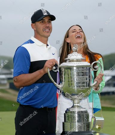 Brooks Koepka, left, poses with the Wanamaker Trophy with his girlfriend Jena Sims after winning the PGA Championship golf tournament, at Bethpage Black in Farmingdale, N.Y