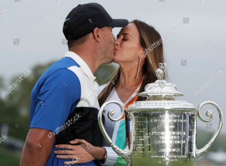 Brooks Koepka, left, kisses his girlfriend Jena Sims after winning the PGA Championship golf tournament, at Bethpage Black in Farmingdale, N.Y
