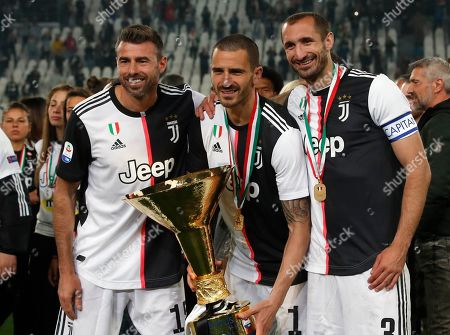 Juventus' Andrea Barzagli, Juventus' Leonardo Bonucci, and Juventus' Giorgio Chiellini, from left to right, pose after winning the Serie A soccer title trophy, at the Allianz Stadium, in Turin, Italy