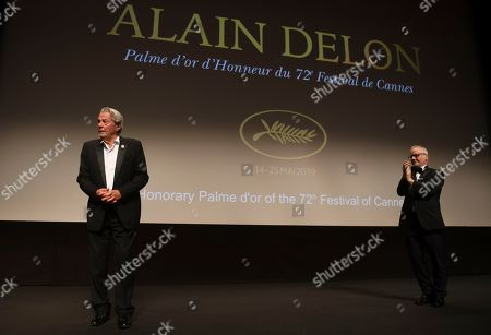 Alain Delon, Thierry Fremaux. Actor Alain Delon accepts applause prior to receiving his honorary Palme D'Or award from festival director Thierry Fremaux, right, at the 72nd international film festival, Cannes, southern France