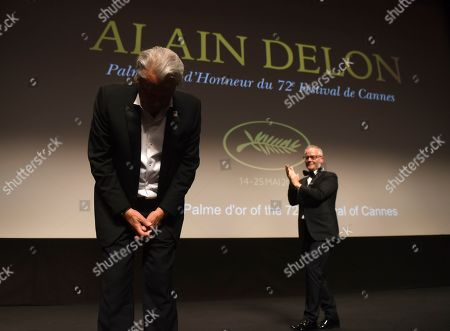 Alain Delon accepts applause prior to receiving his honorary Palme D'Or award from festival director Thierry Fremaux, right, at the 72nd international film festival, Cannes, southern France
