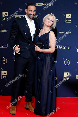 Stock Picture of Soccer player Adil Rami and US actress Pamela Anderson pose as they arrive at the UNFP (Union of French Professional Footballers) ceremony, in Paris, France