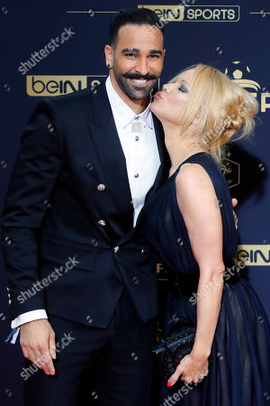 Soccer player Adil Rami and US actress Pamela Anderson pose as they arrive at the UNFP (Union of French Professional Footballers) ceremony, in Paris, France
