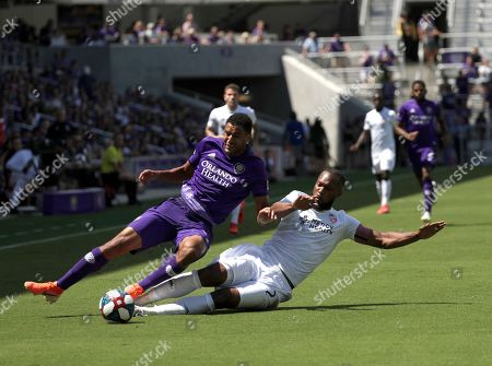Orlando City's Tesho Akindele, left, and FC Cincinnati's Kendall Waston battle for possession of the ball during the first half of an MLS soccer match, in Orlando, Fla