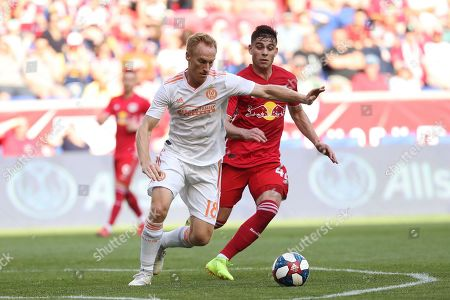 Atlanta United midfielder Jeff Larentowicz, left, keeps the ball away from New York Red Bulls forward Brian White during the first half of an MLS soccer match, in Harrison, N.J