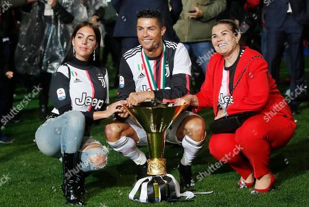 Juventus' Cristiano Ronaldo, center, is flanked by his girlfriend Georgina, left, and his mother Dolores Aveiro, right, pose with the Serie A soccer title trophy, at the Allianz Stadium, in Turin, Italy