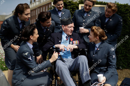 Stock Photo of World War II British D-Day veteran Bernard Morgan, aged 95, who was a sergeant decoder in the Royal Air Force 83 Group Control Centre and landed at Gold beach on the afternoon of June 6, 1944, speaks to the 'D-Day Darlings' singing group after they posed for a group photograph on the 'D-Day 75 Garden', for the 75th anniversary of D-Day at the RHS (Royal Horticultural Society) Chelsea Flower Show, in London, . World-renowned and quintessentially British, the annual show is a celebration of horticultural excellence and innovation