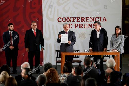 Stock Photo of Mexican President Andres Manuel Lopez Obrador (C) holds the decree that will eliminate taxes exemption for big companies during his daily morning press conference at the National Palace, in Mexico City, Mexico, 20 May 2019. The Mexican Government exempted big companies from paying 20.9 billion dollars in taxes between 2007 and 2018, during the terms of Felipe Calderon and Enrique Pena Nieto.