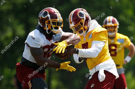 Stock Image of Craig Reynolds, Dwayne Haskins Jr. Washington Redskins quarterback Dwayne Haskins Jr., right, hands off to running back Craig Reynolds during a practice at the team's NFL football practice facility, in Ashburn, Va