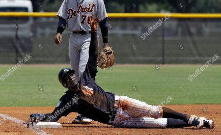 New York Yankees' Didi Gregorius calls for time out after sliding into third base during the first inning of a Gulf Coast League baseball game, in Tampa, Fla. Gregorius is playing for the first time since having Tommy John surgery