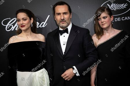 Gilles Lellouche, Marion Cotillard and a guest pose for photographers upon arrival at the Chopard Trophee event at the 72nd international film festival, Cannes, southern France